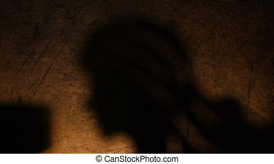 Angel's shadow lit by candle on grunge background
