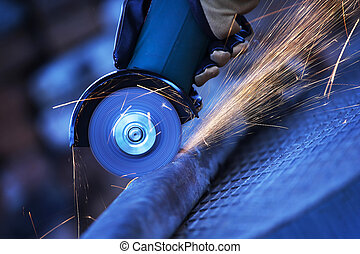 Angle grinder cutting steel - Construction worker using an ...