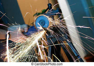 Angle grinder in use, cutting pipes for waterwork. -...