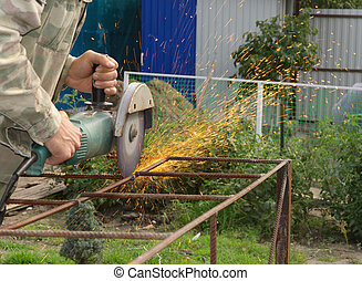 Angle Grinder Metal sawing with flashing sparks close up and Repairman hands home repair garden working summer time. Also called Circular Saw handheld electric instrument