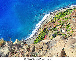 Angle view of the steep coast of the Atlantic island of Madeira down to the colorful rocky coast and the blue sea
