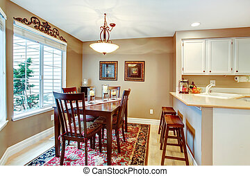 Angled dining room with hardwood floor and rug. Furnished with dining table set and counter stools