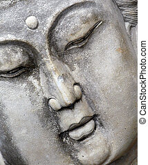 Buddist statue of woman meditating shows calm face and closed eyes. Closeup and angled image of statue.