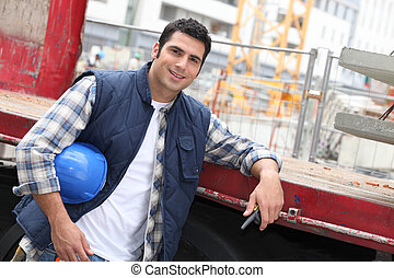Angled shot of construction worker leaning on a truck