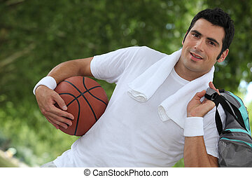 Angled shot of man with basketball and kit bag