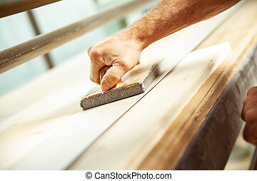 Angled view of man using wood sander with handle