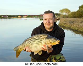 angler with carp in twilight sky - angler with carp to 15...