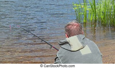 Angler with fishing rod sits at the water