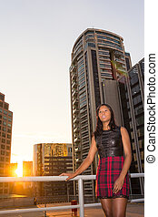 Angles from bottom to top, woman wearing plaid skirt.