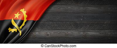 Angola flag on black wood wall. Horizontal panoramic banner.