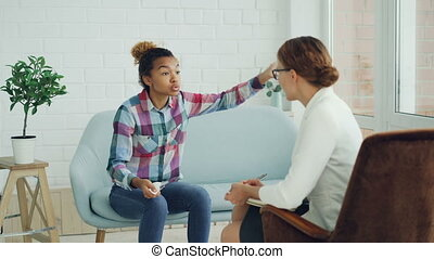 Angry African American lady is speaking with psychologist...