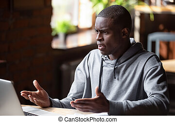 Angry African American man looking at laptop, receiving bad news