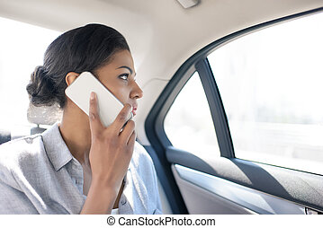 angry african american woman using smartphone in taxi