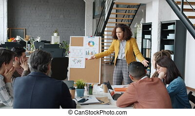 Angry African American woman yelling at employees pointing at board with charts during business meeting