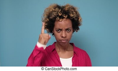 Angry african woman being displeased pointing with finger up on blue background