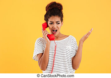 Angry african woman screaming while talking on red telephone...