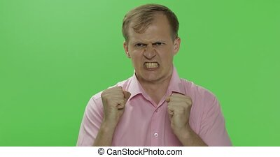 Angry aggressive young man in shirt nervous emotions. Chroma...