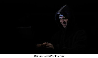 Angry anxious hacker computer programmer in hood attacking cyber security servers and nodding while digital data is reflected on his face