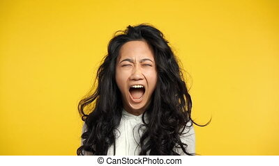 Angry asian woman screaming on yellow background. Negative...