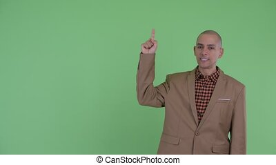 Angry bald multi ethnic businessman pointing up - Studio...