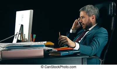 Angry bearded businessman having emotional stressful conversation on his cell phone. Black background.