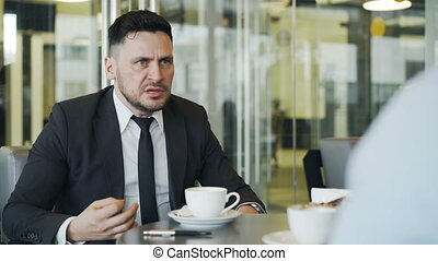 Angry bearded Caucasian businessman striking the table with his pen and scolding his employee for job mistakes in modern cafe.