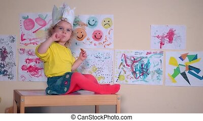 Angry beautiful kid eating cookie sitting on table against paintings on wall