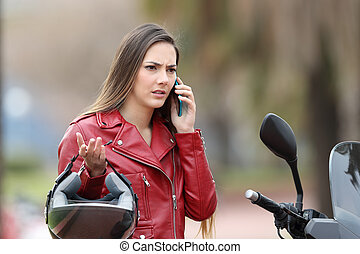 Angry biker calling insurance on phone