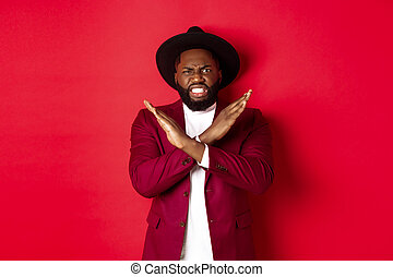 Angry Black man showing cross to stop something, looking furious and declining offer, standing in party clothes, red background