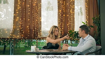 Angry woman checks messages on smartphone of young boyfriend sitting at table in decorated with garlands restaurant