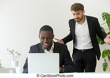 Angry boss catching african employee entertaining online instead