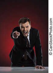 Angry boss. Furious young businessman pointing at camera and shouting while isolated on red