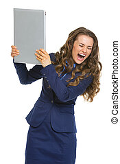 Angry business woman breaking laptop