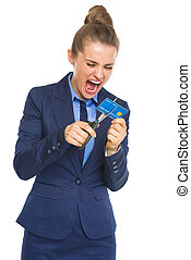 Angry business woman cutting credit card with scissors