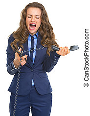 Angry business woman cutting phone handset with scissors