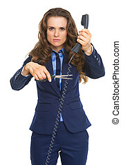 Angry business woman cutting phone wire