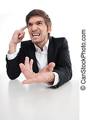 Angry businessman. Angry young businessman shouting and gesturing while isolated on white
