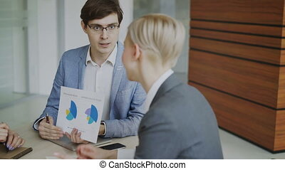 Angry businessman disappointed with company financial reports and scolding female employee sitting at the table in meeting room