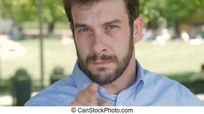 Angry businessman looking and pointing his finger directly at camera