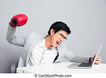 Angry businessman reading to hit the laptop - Angry young...