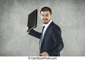 angry businessman ready to destroy a laptop