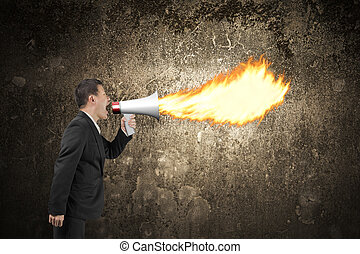 Angry businessman screaming into megaphone spitting fire illuminated dark wall
