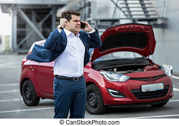Angry businessman shouting in phone because of broken new car