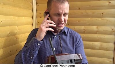 angry businessman shouting in the phone and then hangs up.