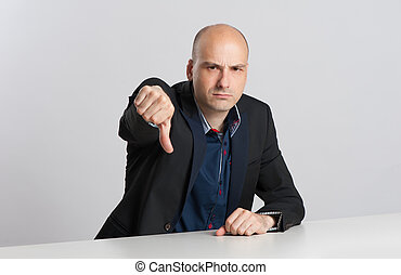 angry businessman shows his thumb down