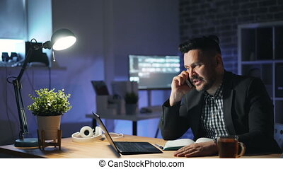 Angry businessman speaking on mobile phone gesturing in dark office at night