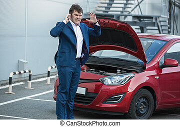 businessman standing next to broken car and calling in service
