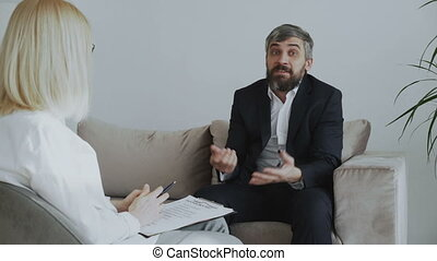 Angry businessman talking about his porblems with female psychologist in her office