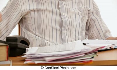 Angry businessman with documents in his office