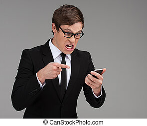 Angry businessman with mobile phone. Furious young businessman holding a mobile phone and pointing it while isolated on grey